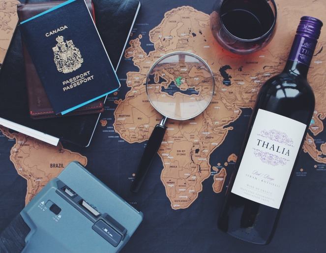 Travel stock image of map, passport, camera, wine, and a magnifying glass